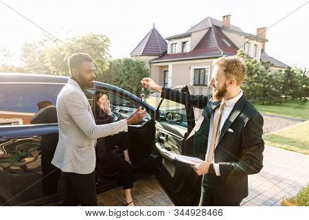 Sales Situation In A Car Dealership Outdoors. Young African Man Gets The Key For The New Car From Ca