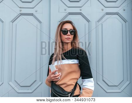 Beautiful Girl In Summer In City, In Her Hand A Mobile Phone, Beige Sweater And Black Glasses. Woode