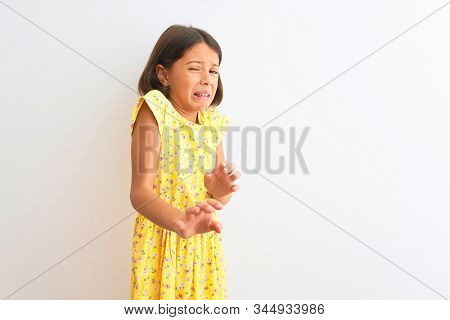 Young beautiful child girl wearing yellow floral dress standing over isolated white background disgusted expression, displeased and fearful doing disgust face because aversion reaction