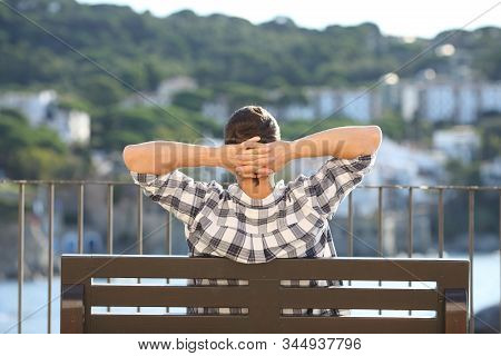 Back View Portrait Of A Man Relaxing Contemplating Views Sitting On A Bench In A Coast Town