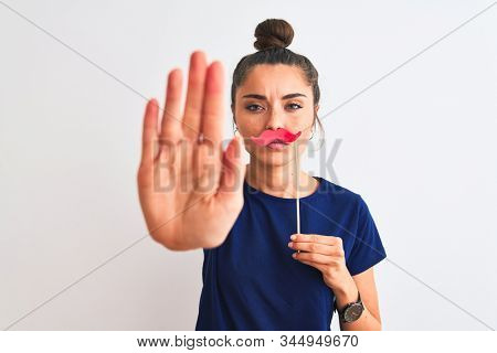 Young beautiful woman holding fanny party mustache over isolated white background with open hand doing stop sign with serious and confident expression, defense gesture