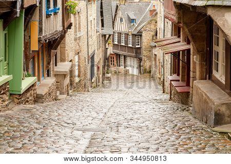 Medieval Cobblestone Rue Du Jerzual Street With Timber-framed Houses And Shops In Historic Dinan, Br