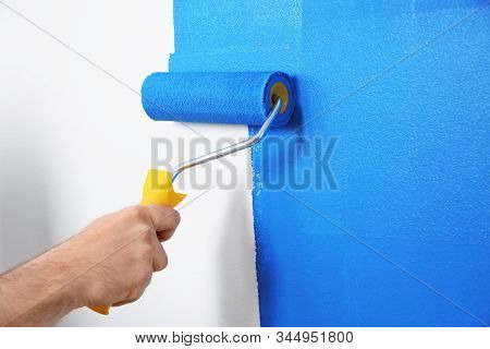Man Painting White Wall With Blue Dye, Closeup. Interior Renovation