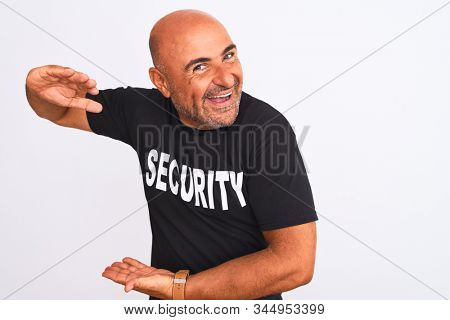 Middle age safeguard man wearing security uniform standing over isolated white background gesturing with hands showing big and large size sign, measure symbol. Smiling looking at the camera. Measuring