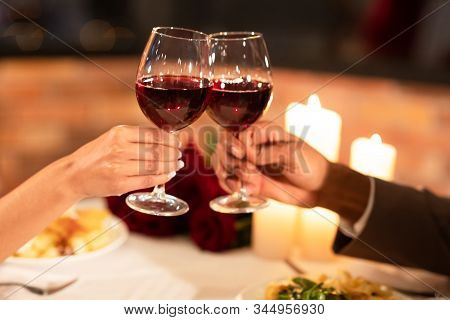 Date In Restaurant. Unrecognizable Boyfriend And Girlfriend Clinking Glasses Drinking Red Wine Durin