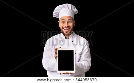 Online Restaurant Menu. Excited Chef Man Showing Tablet Blank Screen Recommending Food Delivery App