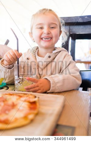 Beautiful toddler child girl sitting on baby highchair drinking juice using straw with happy face