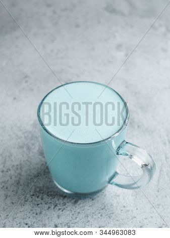 Trendy Drink: Blue Latte. Top View Of Hot Butterfly Pea Latte Or Blue Spirulina Latte On Gray Cement