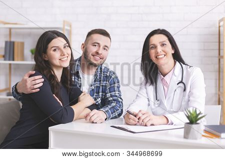 Family Therapist. Cheerful Patients Sitting With Doctor At Annual Medical Checkup In Clinic