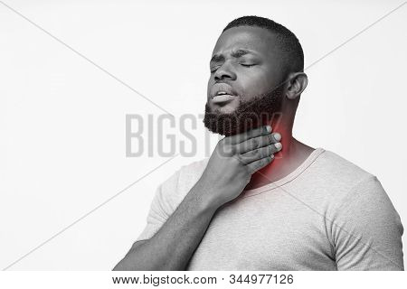 Afro Man Touching His Inflamed Throat, Having Pain, Laryngitis Concept, Monochrome Photo, Free Space