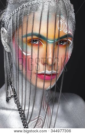 Beautiful Girl In An Unusual Winter Look With Colorful Face. Creative Make- Up. Art Look.