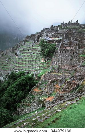 Amazing view of majestic Machu Picchu temple landscape covered with fog on the background