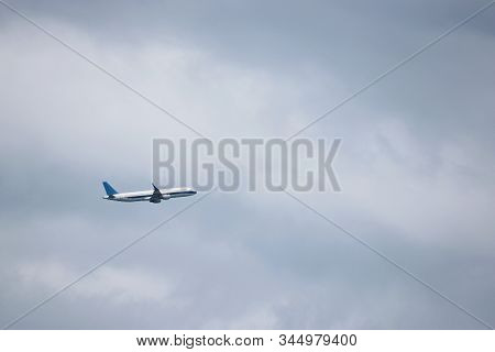 Airplane Flying In The Sky On Background Of White Clouds, Side View. Twin-engine Commercial Plane Du