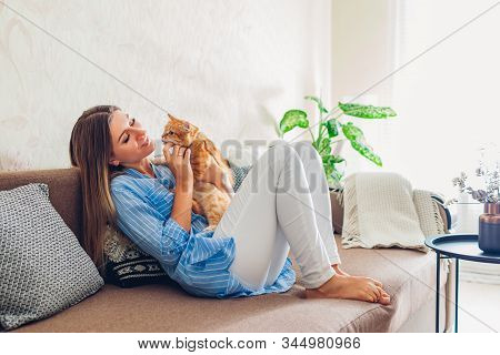 Playing With Cat At Home. Young Woman Sitting And Relaxing On Couch In Living Room And Hugging, Play