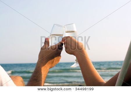 Two Hands Holding Glasses At The Beach