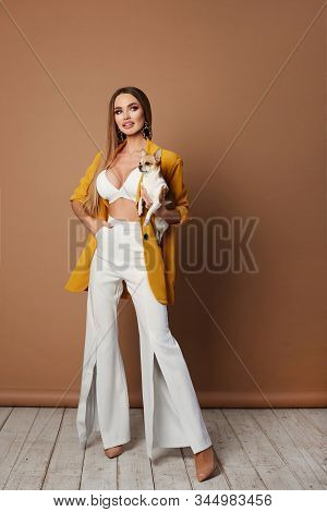 Longlegged Young Woman, With Sexy Perfect Body And Full Lips, In Yellow Jacket And Sexy Lingerie Sit