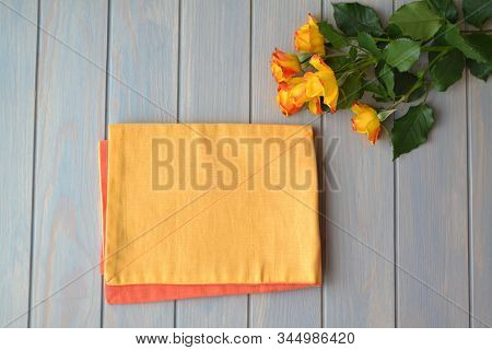 Romantic Dinner Background With Yellow Roses And Serviette On Pastel Blue Background, Top View, Plac
