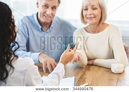 Asthma Attacks. Unrecognizable Nurse Giving Blue Inhaler To Smiling Mature Couple, Selective Focus