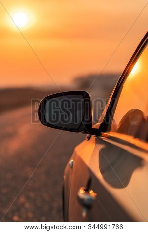 Side View Mirror Of Car On Road In Autumn Sunset For Travel, Car Insurance Or Roadside Assistance Co