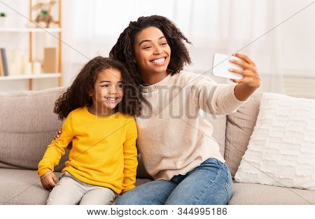 Family Selfie. Happy Black Mother And Daughter Using Smartphone Making Self-portrait Sitting Togethe