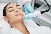 woman receiving no-needle high frequency mesotherapy at beauty salon. non-invasive procedure for skin rejuvenation poster