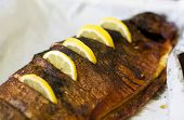 very appetizing smoked trout with segments of lemon poster