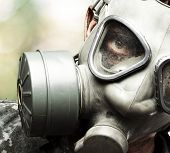 portrait of a young soldier wearing a gas mask against a nature background poster