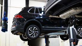 A Modern Car Suv In A Service Center Is Lifted On A Lift For Diagnosis, Maintenance Or Repair. New S