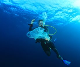 Young woman scuba diver picks up plastic trash from ocean. Beach cleanup concept