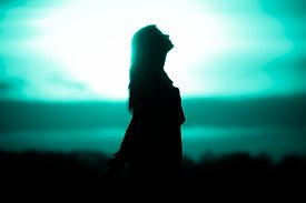 Youth Woman Soul Turquoise Sun Meditation Awaiting Future Times. Silhouette In Front Of Sunset Or Su