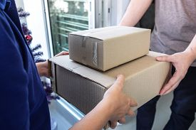 Young Delivery Man Deliver Box Parcel Package And Sending To Customer In Front Of The House And Man