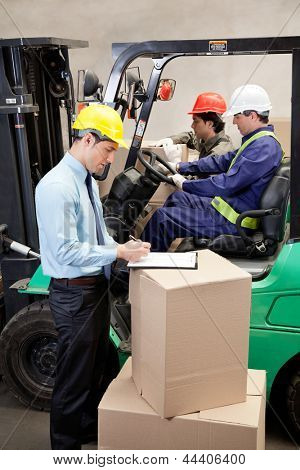 Supervisor writing on clipboard with foremen working at warehouse
