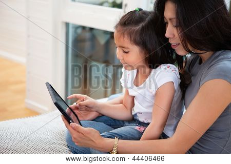 Mother and daughter reading electronic book at home