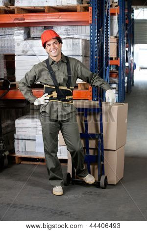 Portrait of young foreman with handtruck loading cardboard boxes at warehouse