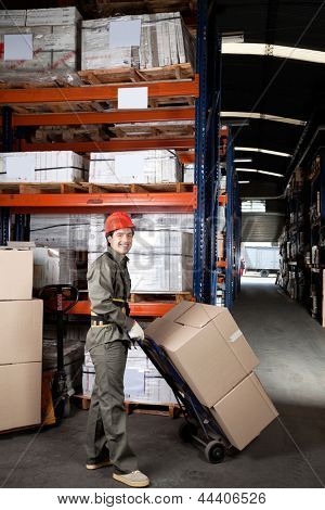 Portrait of young foreman pushing handtruck with cardboard boxes at warehouse