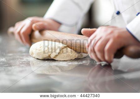 Chef preparing dough in a kitchen