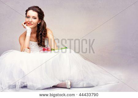 schöne Braut, die auf dem Boden sitzend
