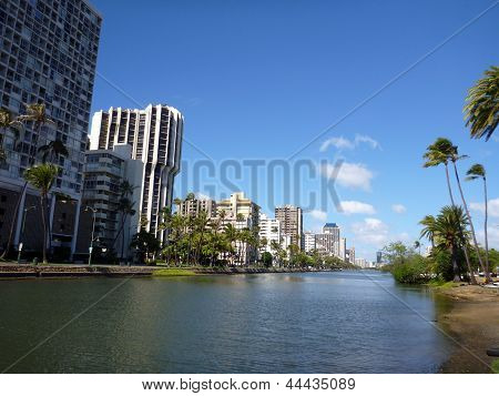 Ala Wai Canal hotels Condos and Coconut trees on a nice day in Waikiki on Oahu Hawaii. poster
