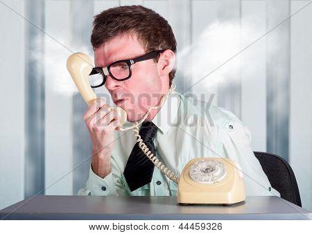 Unhappy Nerd Businessman Yelling Down Retro Phone