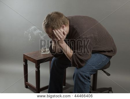 Depressed Young Man Sitting On A Chair, Smoking Holding His Head In His Hands