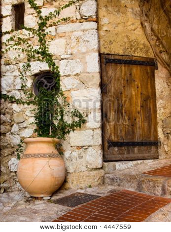 Old wooden door and pot with plant in the medieval city of Exe France which is a fortress built on cliff-side hill poster