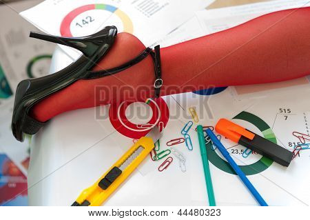 Leg In Red Stocking On Table With Charts