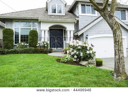 Residential Home In Mid Spring Season With Blooming Flowers And Plush Green Grass