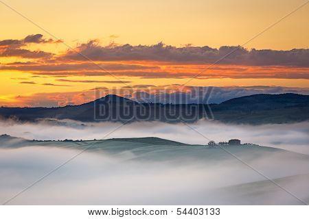 Farmhouse near in Val d'Orcia at foggy dawn, Tuscany, Italy