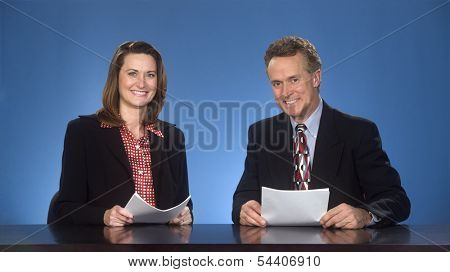 Male and female newscasters sitting at desk smiling at viewer.