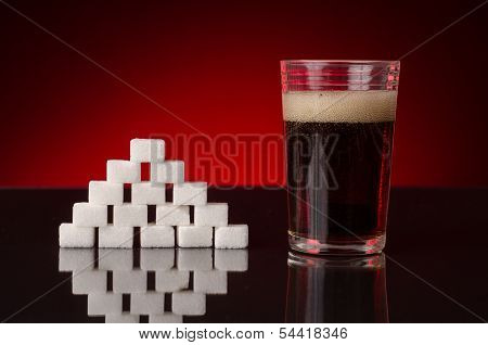 soda with bubbles in a glass, next to a pyramid of sugar cubes