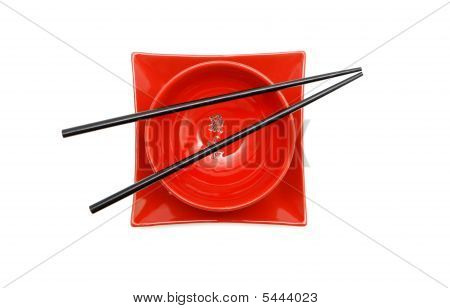 Black Chopsticks On Red  Bowl And Square Plate Top View Isolated