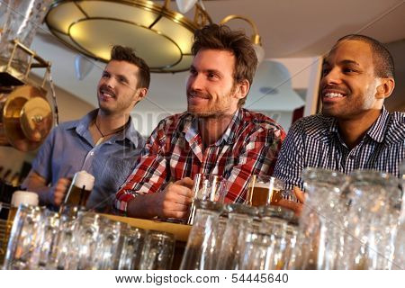 Portrait of young men drinking beer at bar counter, smiling.