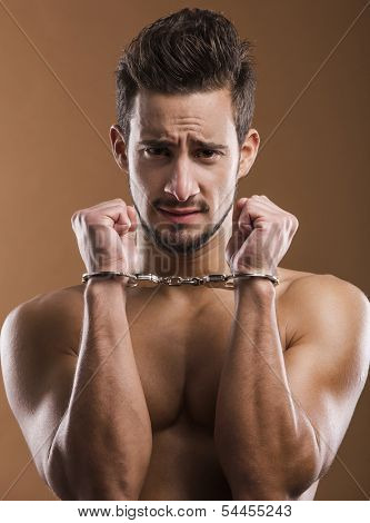 Handsome young man arrested with handcufs on his hands
