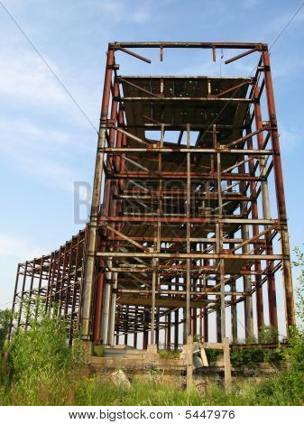 incomplete construction of the production metal structures on the background of the sky. poster